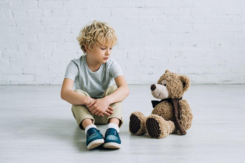 Παιδί κάθεται με το αρκουδάκι του, ανελκόμενοι όρχεις